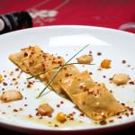 Zuza – Ravióli no Dendê Ravióli de dendê recheado com paçoca de camarão e castanha do Pará. Ao azeite e alho de pimenta comari coberto com Battarga ralada.
